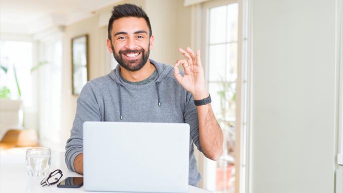 Auf diesem Bild sehen Sie einen Mann der mit seinem Laptop im Homeoffice ist. Er gibt mit seiner linken Hand ein Zeichen, dass es ihm gut geht.
