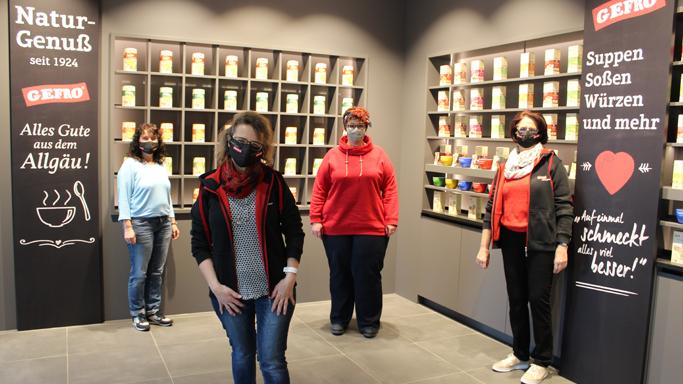 Auf diesem Bild sehen Sie vier Frauen. Im Hintergrund stehen GEFRO-Dosen in zwei Regalen in der Empfangshalle.