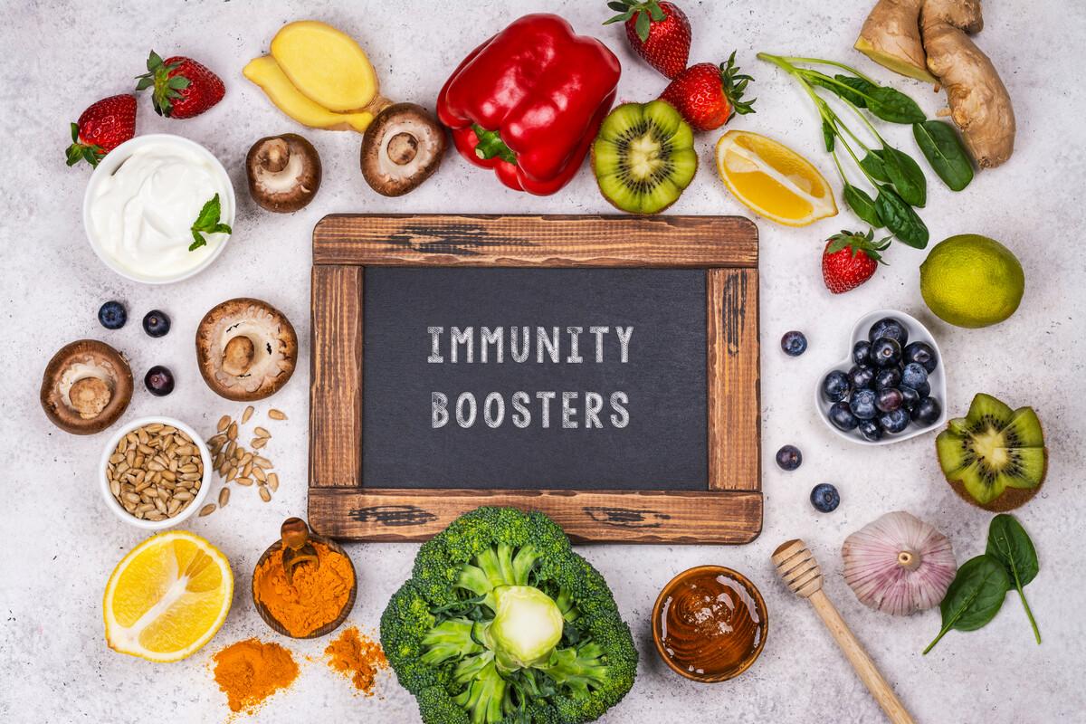 """Auf diesem Bild sehen Sie viele verschiedene Gemüse, Obst und Fruchtsorten wie Brokkoli, Paprika, Kiwis, Trauben, Zitronen, Honig, Zwiebel, Pilze, Körner, Erdbeeren. In der Mitte ist eine Tafel auf der geschrieben ist: """"Immunity Boosters"""""""