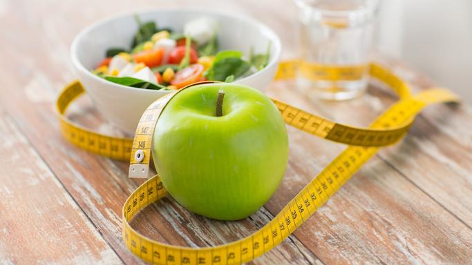 Auf diesem Bild sehen Sie ein Abmessband, das zusammen mit einem Apfel und Gemüse auf einem Tisch steht