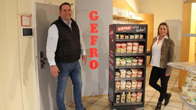 Auf diesem Bild sehen Sie einen Mann und eine Frau die im GEFRO-Laden in Memmingen. Sie stehen beide neben einem Produkt-Aufsteller in dem viele verschiedene GEFRO-Produkte entahlten sind.