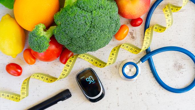 Auf dem Bild sehen Sie Gemüse (Brokkoli & Tomaten) und Früchte (Orange, Zitrone). Ein Blutzuckermessgerät, Testoskop und ein Messband sind außerdem auf dem Bild zu sehen