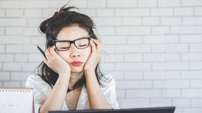 Auf diesem Bild sehen Sie eine Frau mit Brille, die vor ihrem Computer einschläft