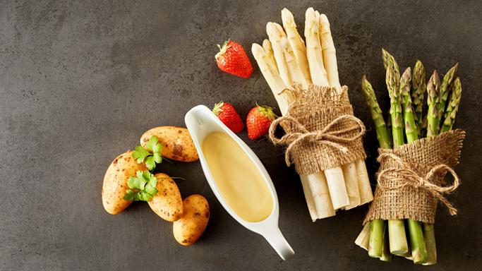 Auf diesem Bild sehen Sie weißen und grünen Spargel. Sie liegen zusammen mit Kartoffeln, Erdbeeren und einer Sauce Hollandaise auf einem schwarzen Tisch.