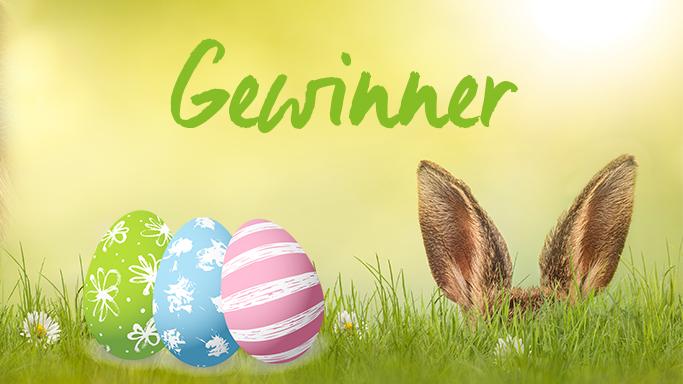 Auf diesem Bild sehen Sie einen Osterhasen der sich im Gras versteckt. Im Bild erkennt man nur seine Ohren. Links daneben liegen drei Ostereier in verschiedenen Farben (Grün, Blau und Rosa)