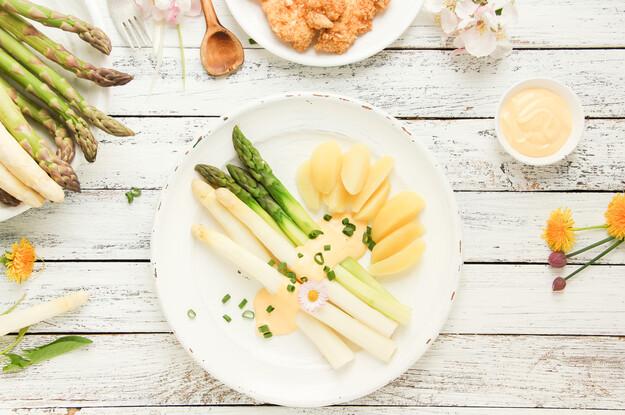 Auf diesem Bild sehen Sie grünen und weißen Spargel und Kartoffeln, der zusammen mit einer Saue Hollandaise auf einem serviert wird. Im Hintergrund steht ein Dipp und weitere grüne und weiße Spargel.