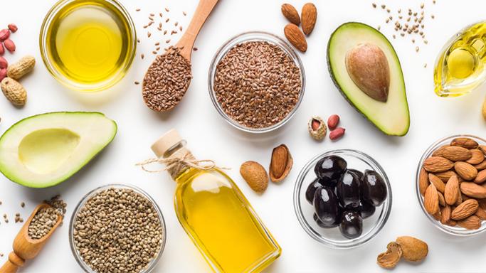 In diesem Bild sehen Sie verscheieden Samen und Kerne, Öle, Oliven, Nüsse und eine aufgeschnittene Avocado.
